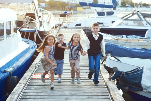 Group of 4 fashion kids wearing striped navy clothes in marine style playing in the sea port