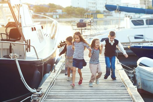 Group of fashion children wearing striped navy clothes in marine style running in the sea port
