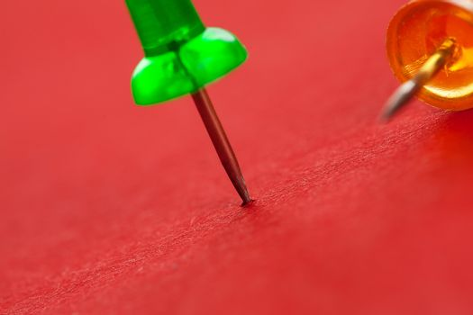 Green and orange pushpins on a red surface