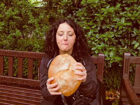 A portrait of hungry pretty young brunette eating huge bread