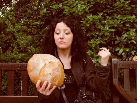 Portrait of pretty young brunette looking at huge bread in hamletic pose - To eat or not to eat