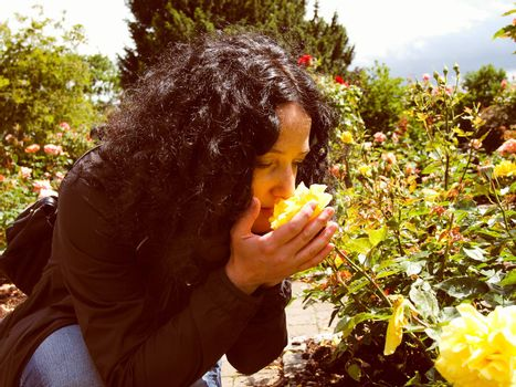 A pretty young brunette girl woman female smelling roses in the garden