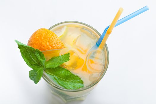 Glass of fresh made non-alcoholic drink citrus lemonade with ice cubes, mint , orange segment and straws. Top view on white background