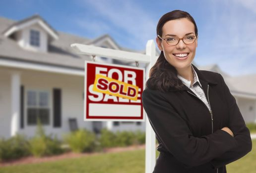 Attractive Mixed Race Woman in Front of House and Sold Real Estate Sign.
