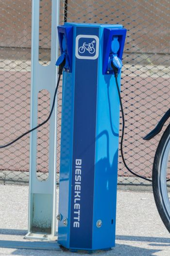 The Hague, Scheveningen Pier, Netherlands - August 7, 2014: Here in the photo the beach promenade of Scheveningen. There are charging point for electric bicycles.  The picture shows an E-Bike which is connected for charging via cable to the station. Here e-bikes are available for rent.