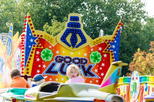 Essen Werden, Nrw, Germany - September 7, 2014: Known September fair, fair in Essen Werden in the parking lot at the church. A group of people, visitors in front of a children's carousel. enjoy the hot late summer day. The name funfair is the abbreviation of the word church weih fair.
