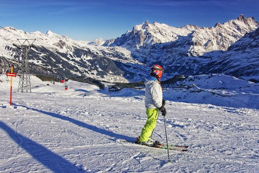 Girl on ski on the mountain slope in swiss alps jungfrau region near cabin car railway on ski resort