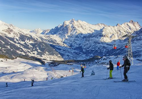 Men and women on ski  and snowboards near cable railway on winter sport resort in swiss alps