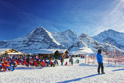 People relaxating at the outdoor lounge on highland winter sport resort in swiss alps