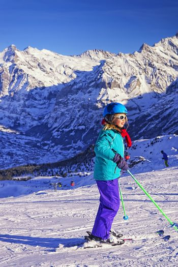 Young blond girl on ski at winter sport resort in swiss alps