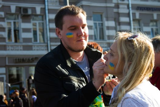 Moscow, Russia - September 21, 2014. Peace March participants draw on their faces Ukrainian flag Peace March in Moscow against war with Ukraine