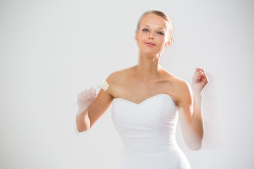 Gorgeous bride dancing, holding a rose