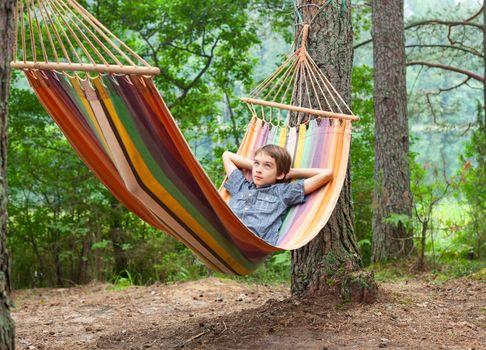 Serene boy lying in striped hammock outdoors