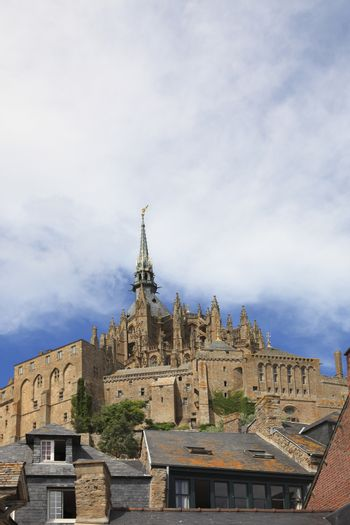 Image of the top of the Monastry from Mountain Saint Michel above the roofs of houses.