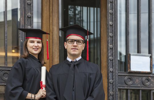 Portrait of a youg couple in the graduation day posing in front of the gate of the University.