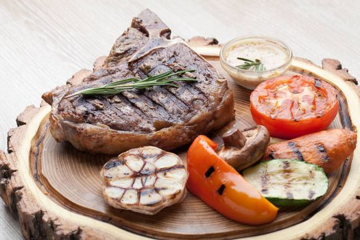Portion of BBQ t-bone steak  served  on wooden board with  rosemary, mustard sauce  and grilled vegetables : tomato, carrot, paprika, garlic,  champignon,  zucchini
