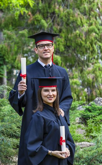 Young couple in the graduation day posing outdoor in a beautiful green garden.