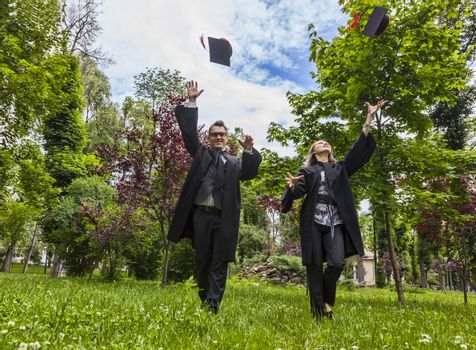 Happy couple in the graduation day running in a park and throwing  their hats up.