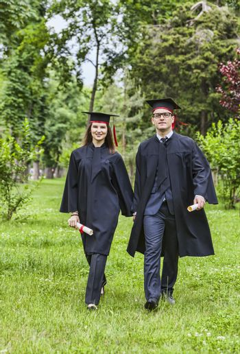 Young happy couple walking hand in hand in a green park in the graduation day.