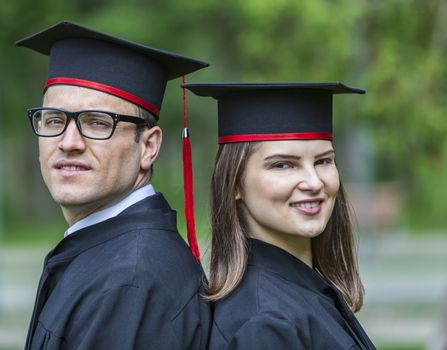 Outdoor portrait of a young couple of students in the graduation day in a park.