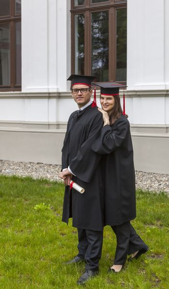 Young couple in the gradutaion day posing outside in front of the University wall.