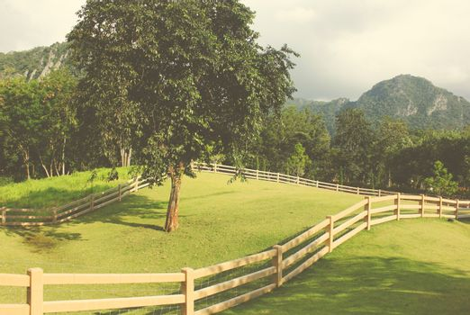 Fence and view of farmland in countryside with retro filter effect