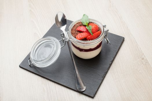 Delicious traditional italian cream dessert pannacotta with grated chocolate, strawberry, and basil served in jar with cocktail spoon on black stone background