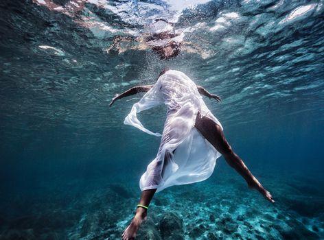 Fashionable model dancing underwater