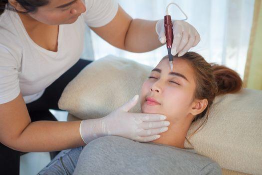 Professional permanent makeup applying on eyebrow