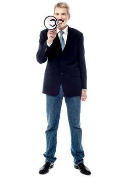 Smiling businessman holding a megaphone
