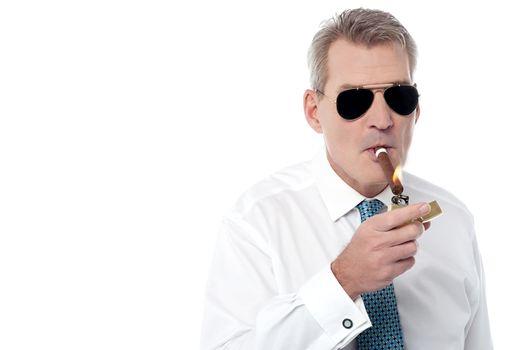 Mature businessman smoking a cigar