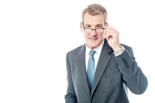 Mature businessman holding eye wear