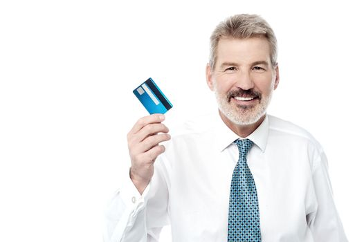 Smiling male executive showing debit card