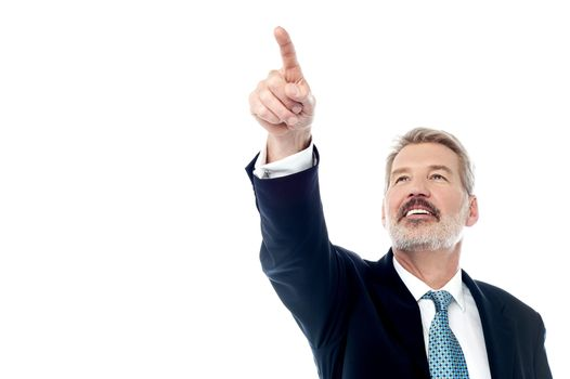Happy businessman pointing at copyspace