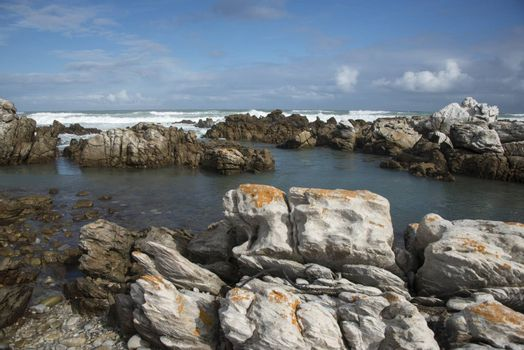 Rocks in the sea at Cape Agulhas eith waves breaking in the background