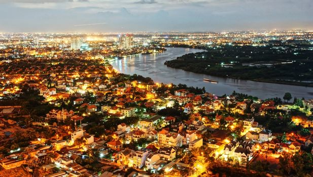 Impression landscape of Ho Chi Minh city from high view, Vietnam at night, city in vibrant, colorful light, houses in new urban along Sai gon river, city bright in electric lamp, so amazing cityscape