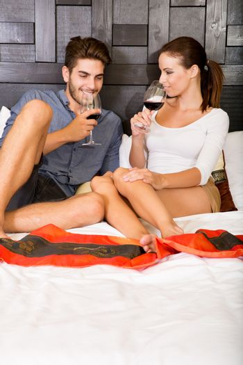 A happy young couple on their vacations with a glass of wine lying on the bed in an asian style hotel room.