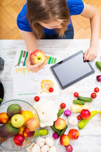 A young adult woman informing herself with a tablet PC about nutritional values of fruits and vegetables.