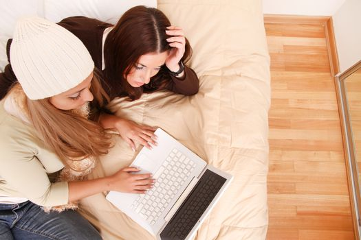 Two girls planning their winter holidays online.