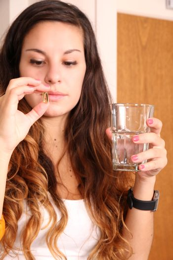 A young woman taking a pill with a glass of water.