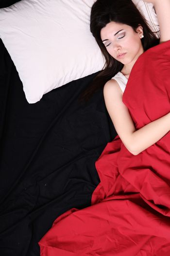 A young hispanic Woman sleeping on the Bed.