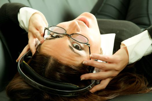 A girl listening to Music with headphones on the sofa.