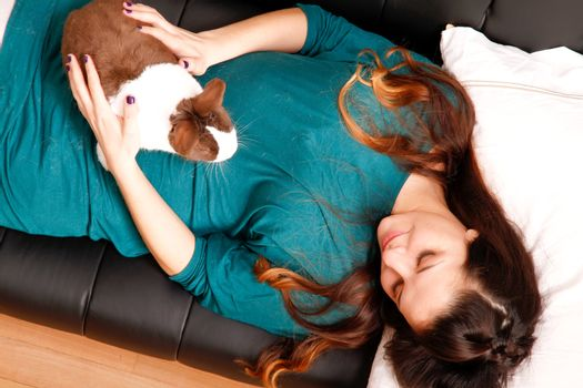 A young hispanic girl with a rabbit on the sofa.