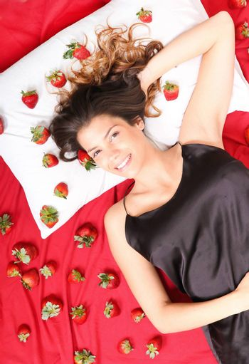 A young adult american woman smiling in a bed full of strawberries.