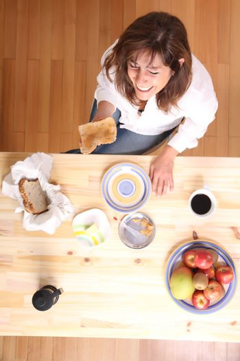 Portrait of a beautiful mature woman sitting in the kitchen.