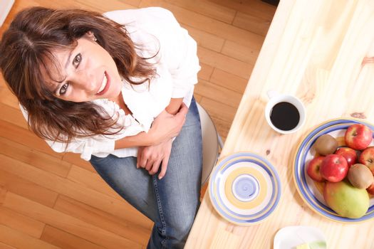 Portrait of a beautiful mature woman sitting in the kitchen. Focus on the Face.