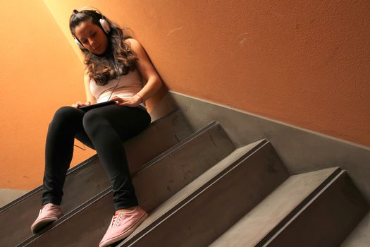 A young woman listening to melancholic Music sitting in the stairway.