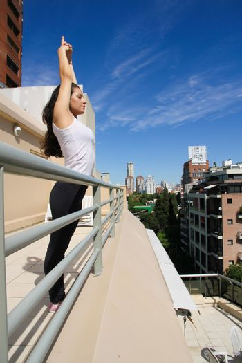 A young adult woman practicing Yoga in an urban environment.