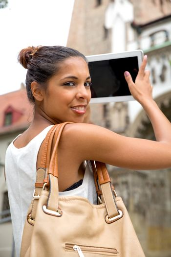 Hispanic girl taking photos of a cathedral with a tablet.