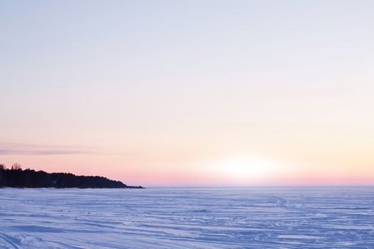Icy surface of the Ladoga lake at sunrise